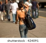 This is a shot of a young lady with several tattoos walking in the city. - stock photo
