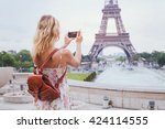 tourist taking photo of eiffel... | Shutterstock . vector #424114555