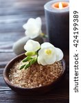 Small photo of Spa composition with alight candles and beautiful flowers on wooden background