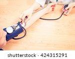 doctor taking pulse of the... | Shutterstock . vector #424315291