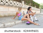 Small photo of Two ethnically diverse teenager girls friends sitting together in suburban home exterior street with white dog pet, using smart phone, outdoors. Active adolescent young women with animal on holiday.