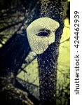 Vintage Venetian Mask on Old Tree by a Pond - stock photo