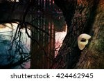 Vintage Venetian Mask on an Old Tree by a Lake - stock photo