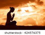 young woman praying in a... | Shutterstock . vector #424576375