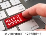 Stock photo finger pressing a modern laptop keyboard key with keep it simple sign finger pushing keep it 424958944
