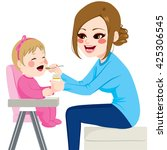 mother feeding baby with spoon... | Shutterstock .eps vector #425306545