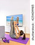 Small photo of Home fitness ab workout in front of television. Girl doing toe touch crunch exercises to train upper abs for a flat stomach while watching a nature TV show or training program living a healthy life.