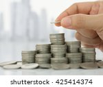 hand putting coin on coins... | Shutterstock . vector #425414374