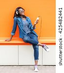 Small photo of Beautiful smiling african woman with headphones listens to music over orange background. Fashion woman in sunglasses outdoor.