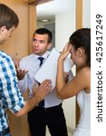 Small photo of Debt collector and young spouses with overdue payment at the doorway