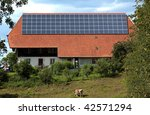 Solar panels on the roof of a house on a farm - stock photo