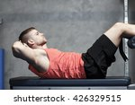 Small photo of sport, fitness, bodybuilding, lifestyle and people concept - young man making abdominal exercises in gym