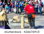 Small photo of Emmaboda, Sweden - May 13, 2016: Forest and tractor (Skog och traktor) fair. Kaha Nui Wood lumberjack sports show. Person sawing circles on a loose standing log.