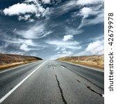 Asphalt Road Under Fluffy Clouds