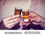 two hands toasting whiskey on... | Shutterstock . vector #427021501