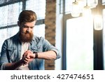 pleasant bearded man using... | Shutterstock . vector #427474651