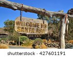 "Small photo of old vintage wood signboard with text "" welcome to Santa Ana"" hanging on a branch"