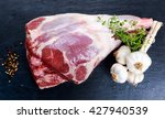 Small photo of Raw lamb leg on blue stone background with herbs