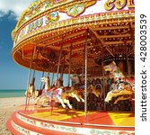 Small photo of Merry Go Round carousel with horses on a beach at a fun fair on a summer sunny day