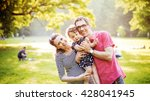 happy family hugging in a park | Shutterstock . vector #428041945