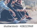 Small photo of Carefree time with best friends. Close-up of group of young smiling people bonding to each other and looking at digital tablet while sitting outdoors together