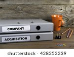 Small photo of Company and Acquisition - two folders on wooden office desk