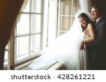 bride laugh while fiance hugs... | Shutterstock . vector #428261221