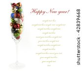 Champagne glass filled with colorful holiday ornaments over white - stock photo
