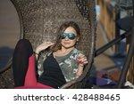 woman sitting on a wicker swing ... | Shutterstock . vector #428488465