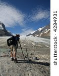 Photographer in front of Athabasca Glacier - stock photo