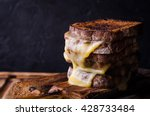 Brown bread toasts with grilled cheese on dark wooden background. Selective focus