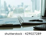 Small photo of The report analyzes the growing business and pen on desk of financial adviser with city in background.
