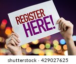 Small photo of Register Here placard with bokeh background
