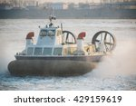 Small photo of Photo of Russian ACV Hovercraft in Action on a Frosen River. Air Cushion Vehicle Blows Water on a Winter Lake
