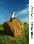 Young female looking to the sunset and sitting on hay bale - stock photo