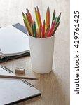 Small photo of Cup white, pencil, eraser, sharpener, calendar, address book, desk.