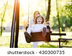 Small photo of Disabled child enjoying the swing outdoors with sister