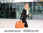 Small photo of Successful businesswoman or entrepreneur walking outdoor with her orange briefcase and bringing her notebook. City business woman working.portrait with vibrant color filter effect