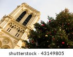 Holiday season in Paris. Large Christmas tree in front of the Notre-Dame de Paris - stock photo