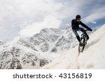 Young Man Biking Down Snowy...