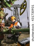 Small photo of Woman engineer in the oil field repairing wellhead with the wrench wearing orange helmet and work clothes. Pump jack and tool box background. Oil and gas concept.