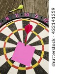 Small photo of Setting and achieving goals: a dartboard with a blank note in the bulls-eye