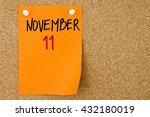 Small photo of 11 NOVEMBER written on orange paper note pinned on cork board with white thumbtacks, copy space available