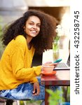 Small photo of Portrait of cheerful african american lady sitting at outdoor cafe with mobile phone and laptop on table