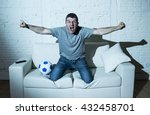 Small photo of young man fanatic and crazy football fan watching television soccer match alone screaming happy celebrating scoring goal in glad and ecstatic face expression with ball on home couch