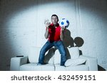 Small photo of fanatic man jumping happy on sofa couch holding money and ball in his hands watching soccer game on television ecstatic and excited winning on line bet in internet gambling concept