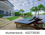 Deck chairs by the pool at waterfront mansion - stock photo