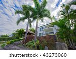 Garden with palms and Bali hut in front of waterfront mansion - stock photo