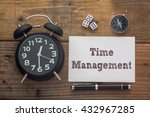 Small photo of Time Management written on paper with wooden background desk,clock,dice,compass and pen.Top view conceptual