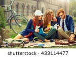 Stock photo young beautiful students are sitting and reading near university 433114477